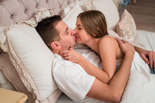 ロマンチックなカップルがベッドでキス