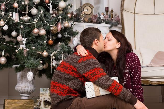彼らはクリスマスイブに彼らの贈り物を祝い、共有しながらクリスマスツリーの前でキスするロマンチックなカップル
