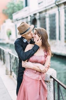 Романтическая пара поцелуи в венеции, италия. девушка в розовом платье и мальчик в шляпе и черной одежде гуляют по улицам венеции