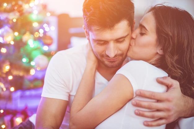 The romantic couple kissing near the christmas tree