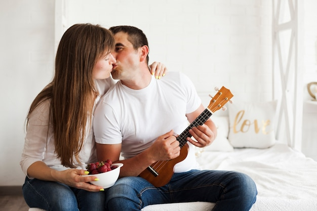 Romantic couple kissing while playing ukulele in bedroom