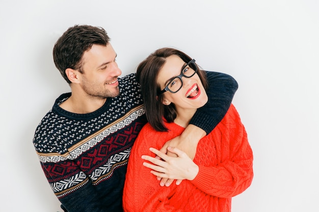 Romantic couple in love embrace each other and have fun together, wear warm knitted sweaters, stand against white