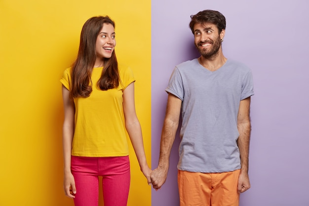 Romantic couple in love have date, hold hands, look positively at each other