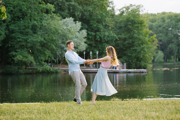 A romantic couple in love holding hands and spinning on the shore of the lake