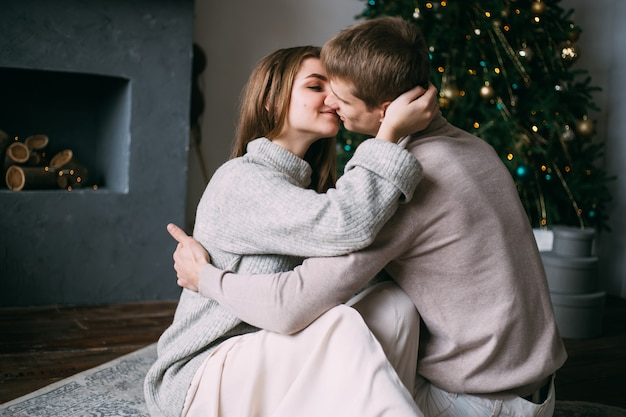 Romantic couple in love kissing near christmas tree at home, new year
