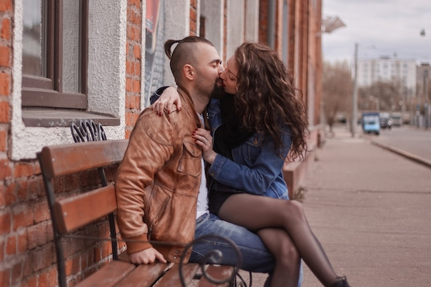 Romantic couple in love kissing, sitting on the bench . the concept of love and relationships