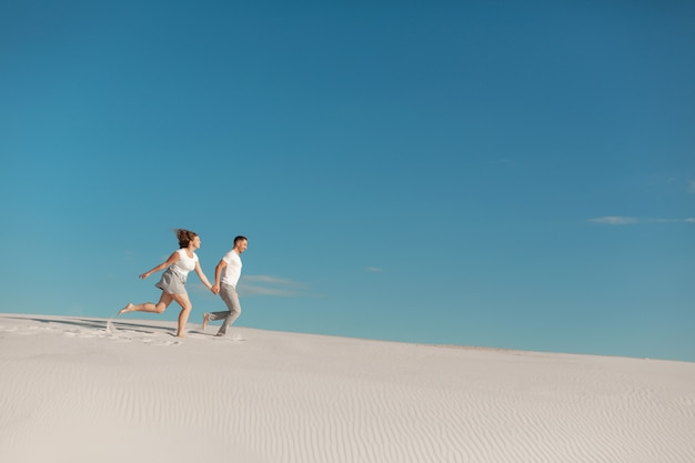 Romantic couple in love running on white sand in desert