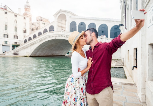 Romantic couple in love on vacation in venice, italy. young people kissing and take a selfie in front of rialto bridge.