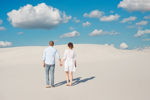 Romantic couple in love on the white sand in the desert.