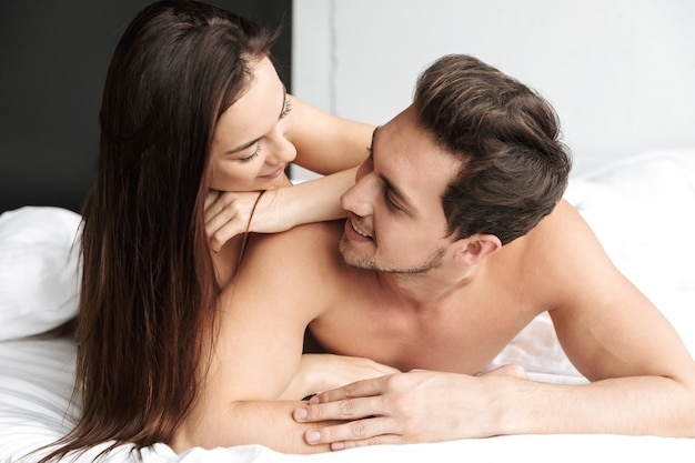 Romantic couple man and woman hugging together, while lying in bed at home or hotel apartment