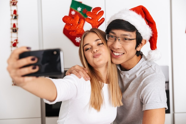 Romantic couple, man and woman wearing christmas outfit, standing in bright kitchen and taking selfie photo on mobile phone