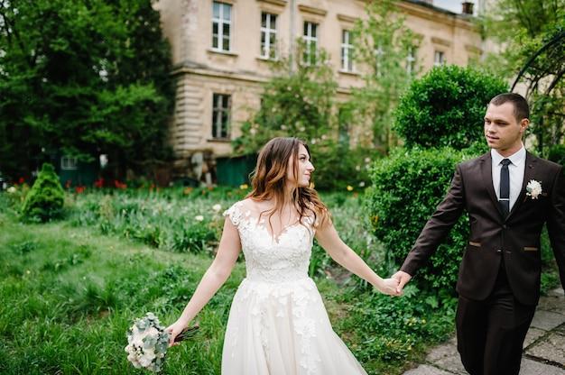 Романтическая пара молодоженов, невеста и жених идет по тропе в зеленом парке. счастливый и радостный момент свадьбы.