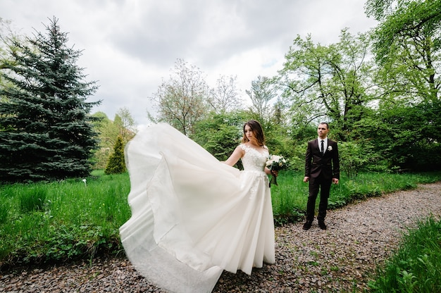 Романтическая пара молодоженов, невеста и жених идет по тропе в зеленом парке.