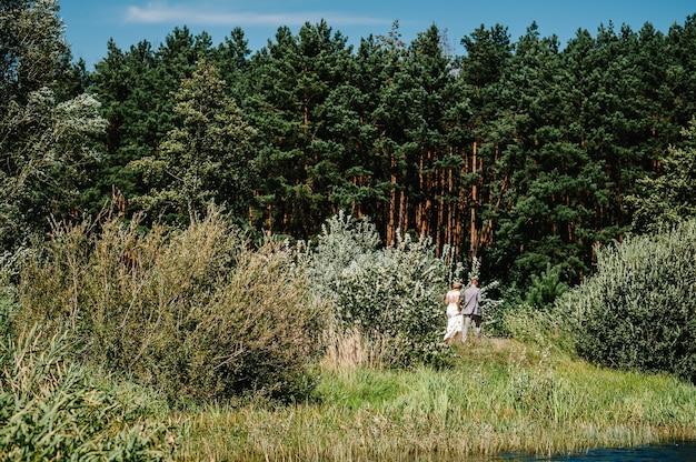 Романтическая пара молодоженов, жениха и невесты прогулки на свежем воздухе. свадебная церемония на природе.