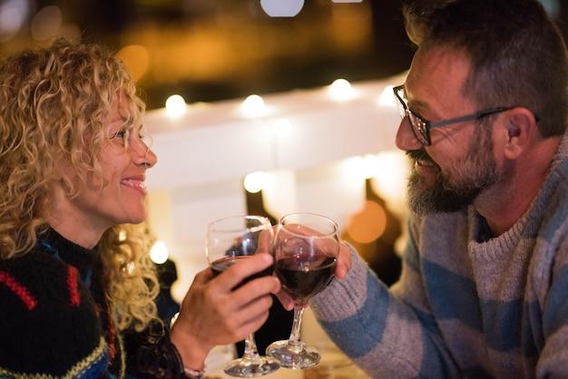 夜にレストランで一緒にワインを食べたり飲んだりして記念日を祝う2人の大人のロマンチックなカップル