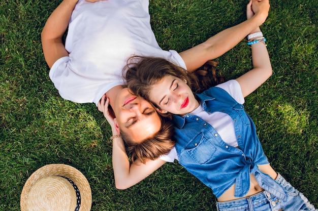 公園の芝生の上で横になっている若者のロマンチックなカップル。彼らはお互いの肩の上に横たわり、手をつないでいます。彼らは目を閉じておくとリラックスして見えます。上からの眺め。