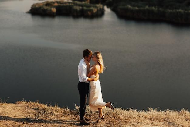 デートのロマンチックなカップル。川のある丘の上に一緒に立っている男性と女性