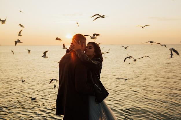 갈매기 비행 표면에 화려한 일몰 해변에서 낭만적 인 커플.