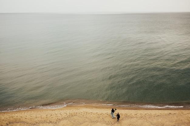 砂浜のロマンチックなカップル。紺碧の水。