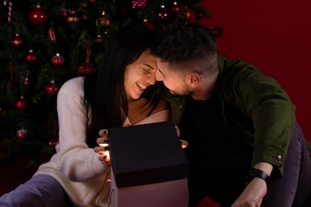 魔法のクリスマスプレゼントを開くロマンチックなカップル
