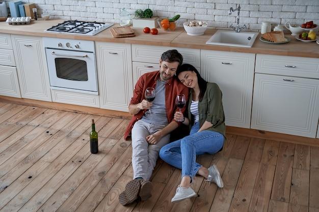 現代の床に座っている若い幸せな男と女の家でリラックスするロマンチックなカップル