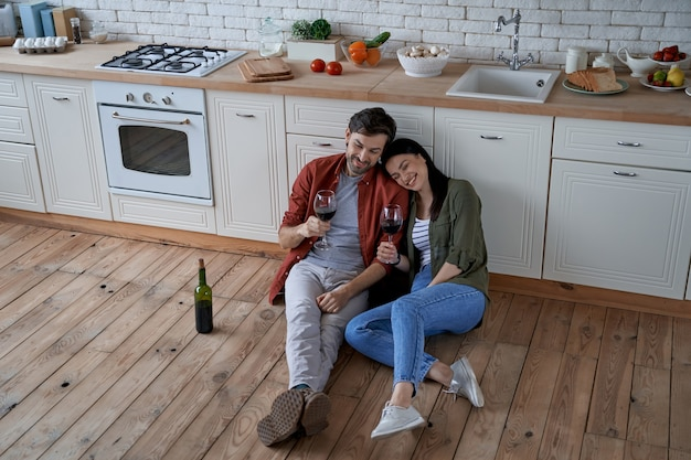 Romantic couple relaxing at home young happy man and woman sitting on the floor in the modern