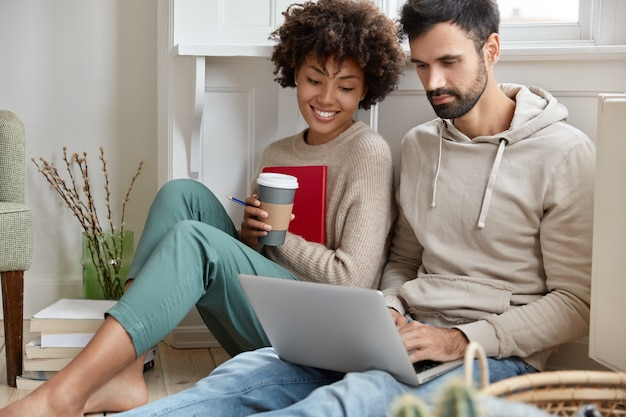 Romantic couple sit closely on floor, focused in laptop computer, watch interesting film online, enjoy aromatic coffee, being in good mood, enjoy wireless internet connection, have spare time