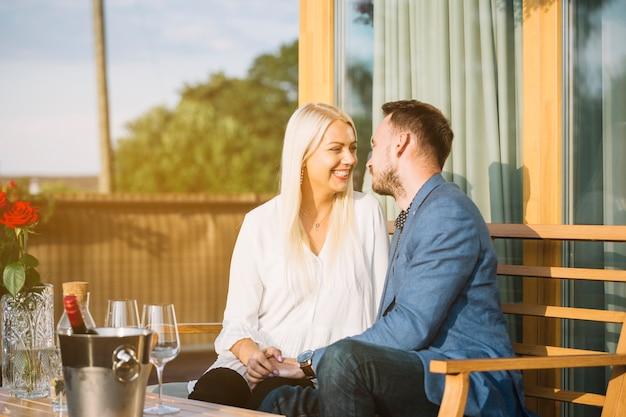 お互いを愛するレストランに座っているロマンチックなカップル