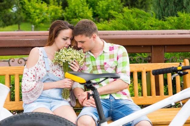 벤치에 앉아 공원에서 꽃 냄새를 맡는 낭만적인 커플은 자전거를 맞은편에 주차했습니다.