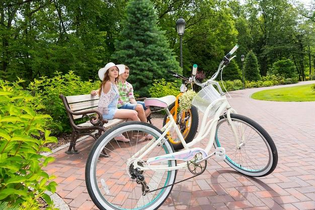 아름다운 녹색 공원의 벽돌 보도에 주차된 자전거 근처 벤치에 앉아 있는 낭만적인 커플