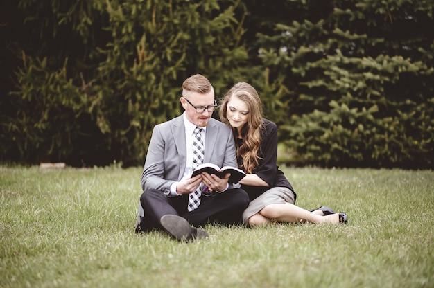 芝生の芝生の上に座って、愛情を込めて本を読んでロマンチックなカップル