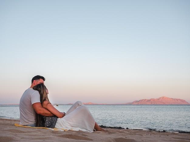 Романтическая пара сидит на пляже и смотрит на море