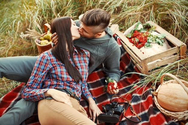ロマンチックなカップルの草の上に座ってキス