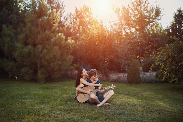 Романтическая пара, сидя на траве в саду