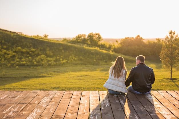 秋の自然の中で桟橋に座っているロマンチックなカップル。