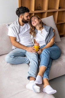 Romantic couple on the sofa at home having juice