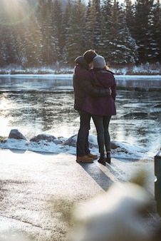Romantic couple standing by river in winter