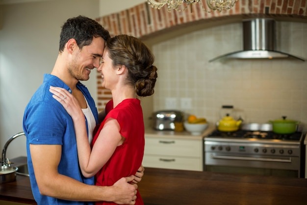 Romantic couple standing face to face and embracing each other in kitchen