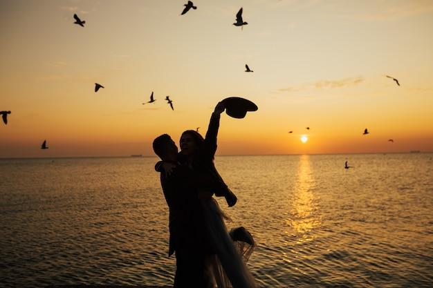ロマンチックなカップルは、太陽の黄金の光線の中で海岸に立って、美しい夕日を楽しみながら一緒に時間を過ごします。