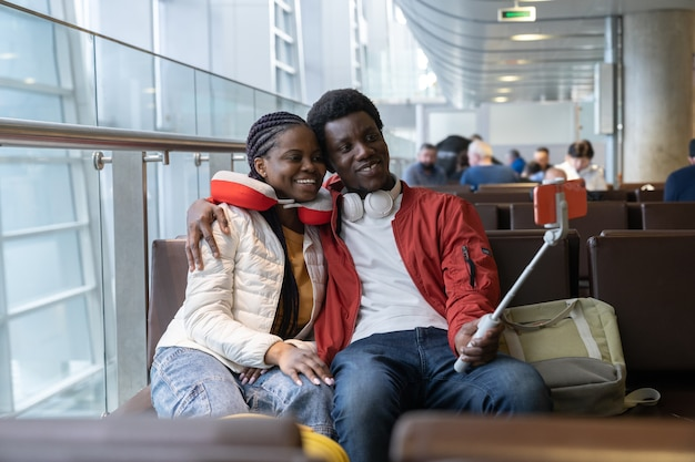 Romantic couple take selfie in airport lounge before flight