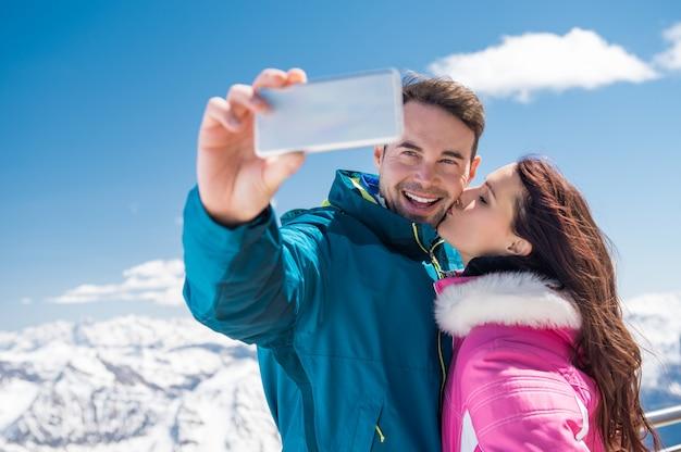 Romantic couple taking snow selfie