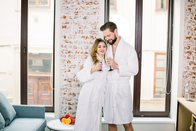 Romantic couple together with champagne glasses at the hotel room