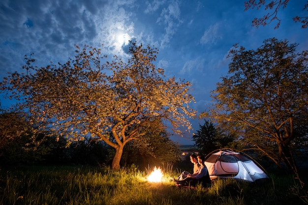 Romantic couple tourists sitting at a campfire near tent under trees and night sky with the moon.