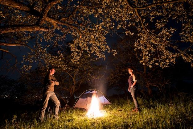 Романтическая пара туристов, стоя у костра возле палатки под деревьями и ночное небо. ночной кемпинг