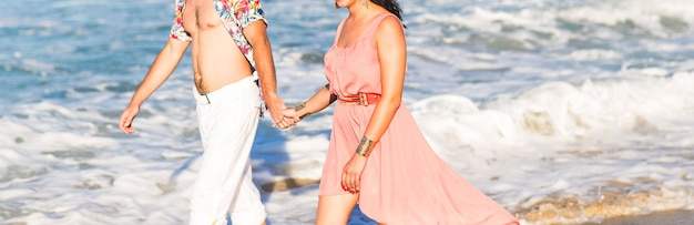 Романтическая пара прогулки на солнечном пляже.
