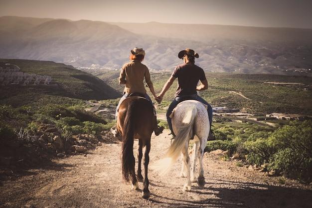 Романтическая пара широких лошадей вместе, держась за руки с любовью и романтикой в альтернативной деятельности на открытом воздухе - вид со спины молодых людей с животными