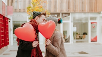 Romantic couple with balloons kissing on street