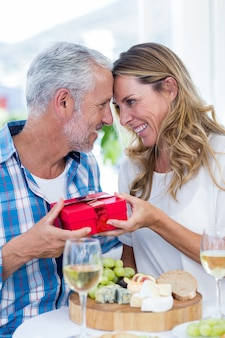 Romantic couple with gift in restaurant