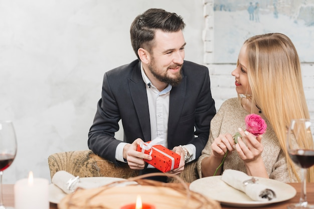 Romantic couple with present and rose