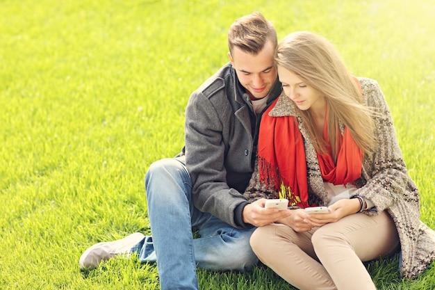 芝生の上のスマートフォンとロマンチックなカップル